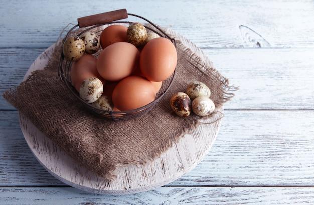 나무 배경에 바구니에 많은 계란