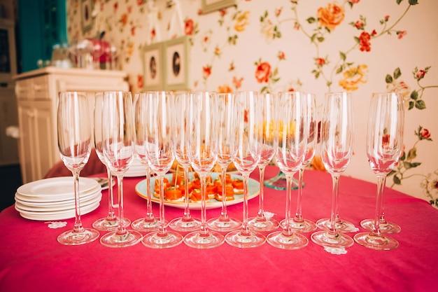多くの空のシャンパングラスをクローズアップ。ピンクのテーブルにガラスのゴブレット。空のクリスタルワイングラス。高い脚にガラスの杯。