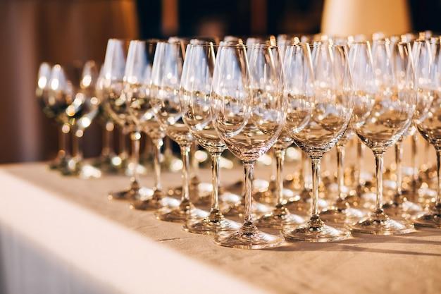 多くの空のシャンパングラスをクローズアップ。白いテーブルの上のガラスのゴブレット。空のクリスタルワイングラス。高い脚にガラスの杯。