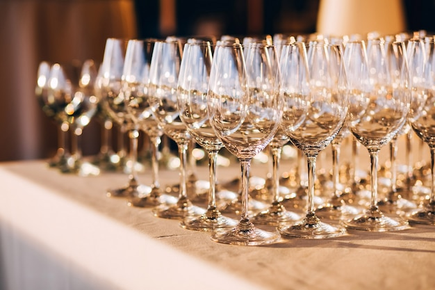 Many empty champagne glasses close up. glass goblets on the white table. empty crystal wineglass. glass goblet on a high leg.