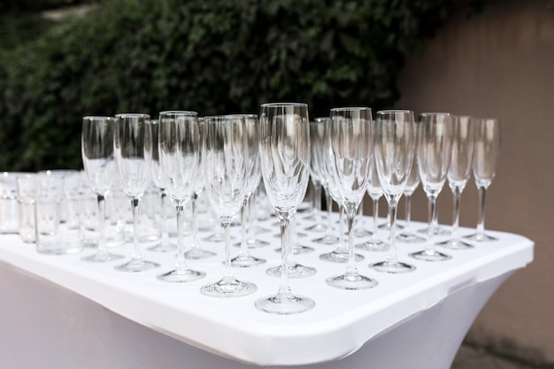 Many empty clean glasses for guests at the buffet festive wedding table