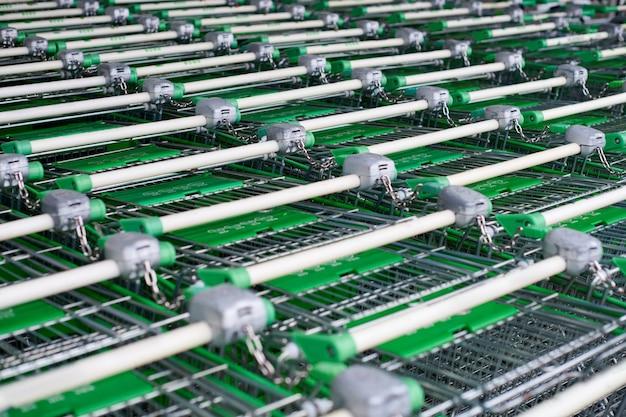 多くの空の緑のショッピングカートが並んでいます。スーパーマーケットに駐車したトロリーの列。