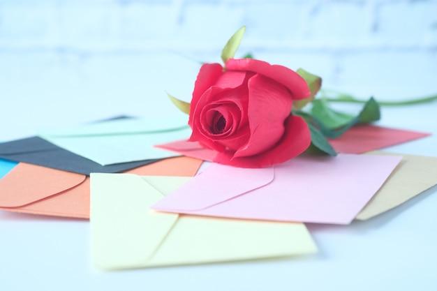 白い背景にたくさんの封筒とバラの花。