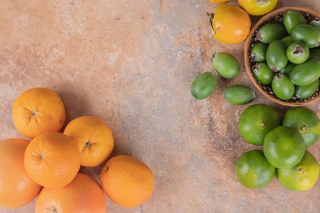 Molti di feijoa, mandarino e arance su marmo.