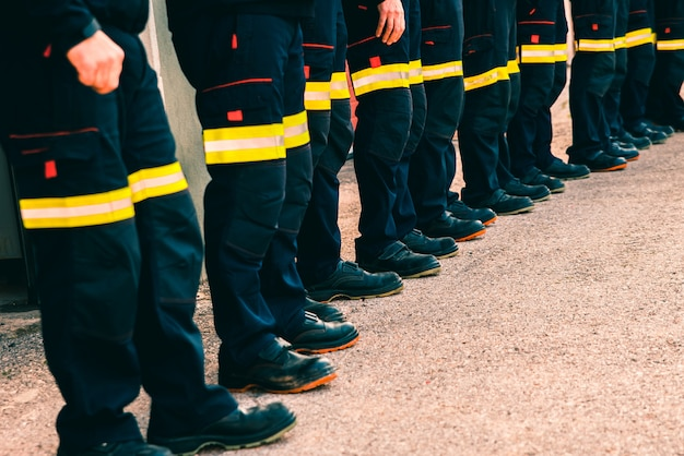 Many firefighters lined up in reflective pants