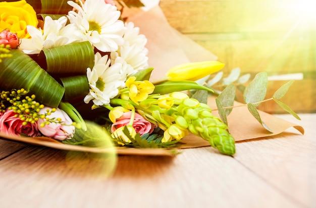 Многие цветы в корзине на фоне солнца. украшение,