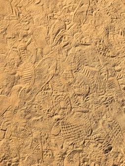 Многие след на фоне текстуры песчаного пляжа.