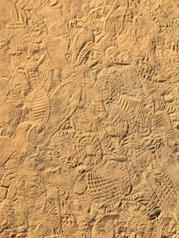 Many footprint on the sand beach texture background.