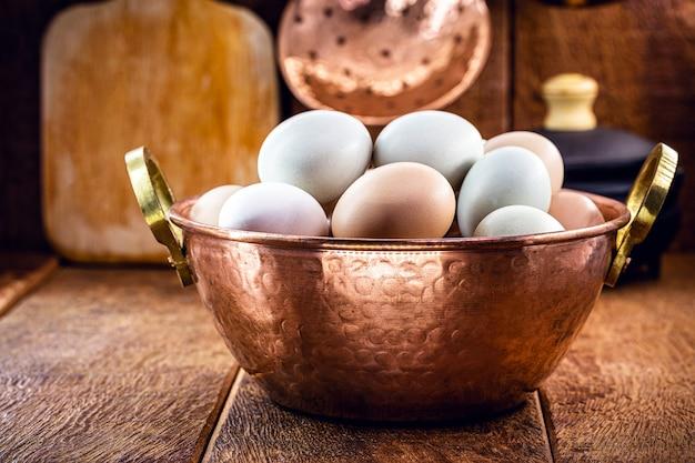 Много яиц от кур на свободном выгуле на деревенской кухне, бразильские яйца в медном горшке