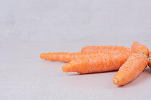 Molte carote fresche sul tavolo bianco