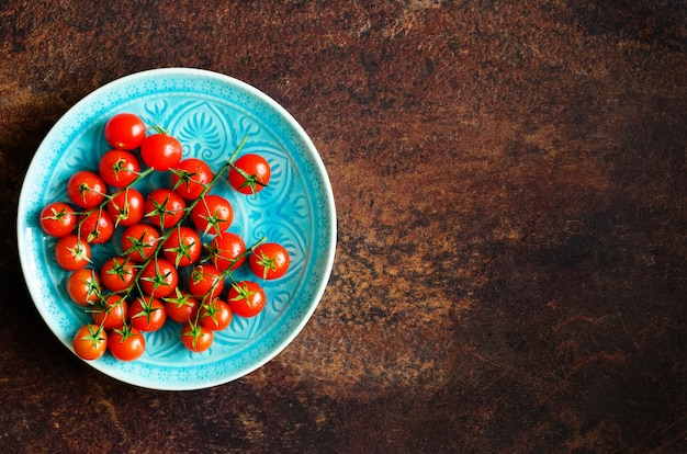 Many fresh cherry tomatoes in blue plate on brown.