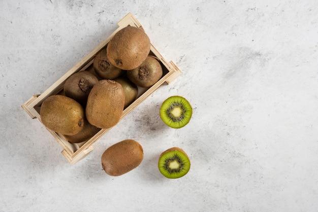 Molti dei kiwi freschi sul cestino di legno.