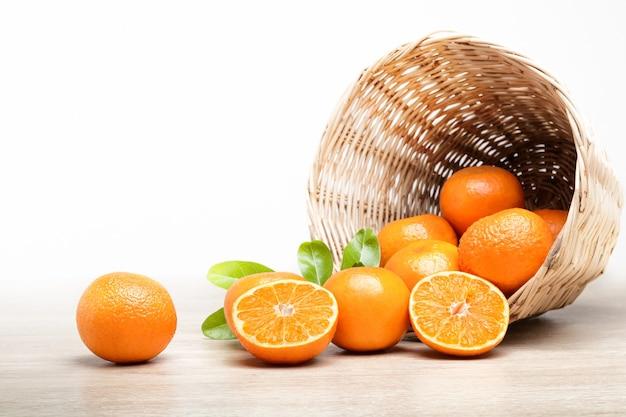 Много свежих апельсинов в деревянной корзине на полу.