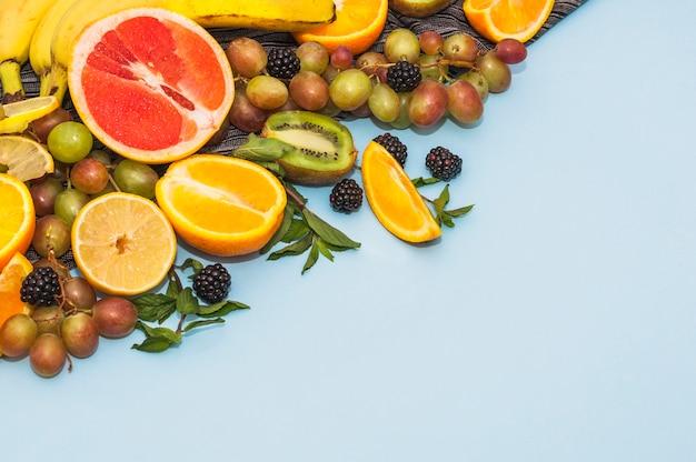 Many fresh organic fruits on blue background