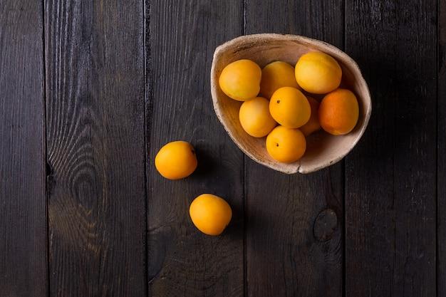 暗い木製のテーブルの背景に粘土板に多くの新鮮な熟したオレンジアプリコット