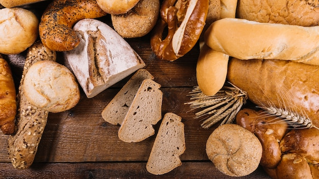 Many freshly baked bread on wooden table