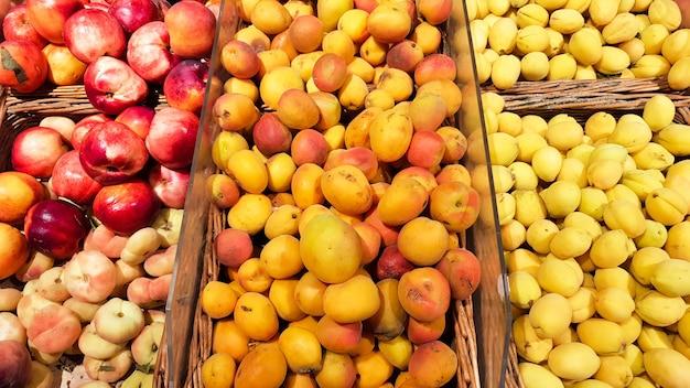 Многие ящики для фруктов продаются на фруктовом рынке. абрикос и персик в витрине магазина