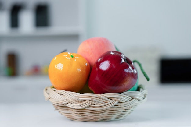 Many fruits in a wooden basket on the table in the kitchen.