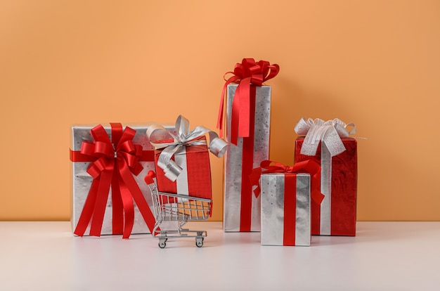 Many gift box with red ribbon bow and shopping cart or trolley on white table and pastel orange wall