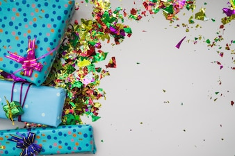 Many gift boxes and confetti on gray background