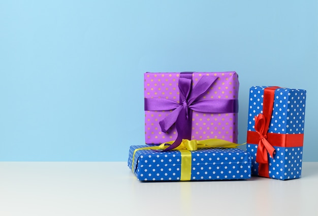 Many gift boxes tied with a silk ribbon on a white wooden table, blue background.