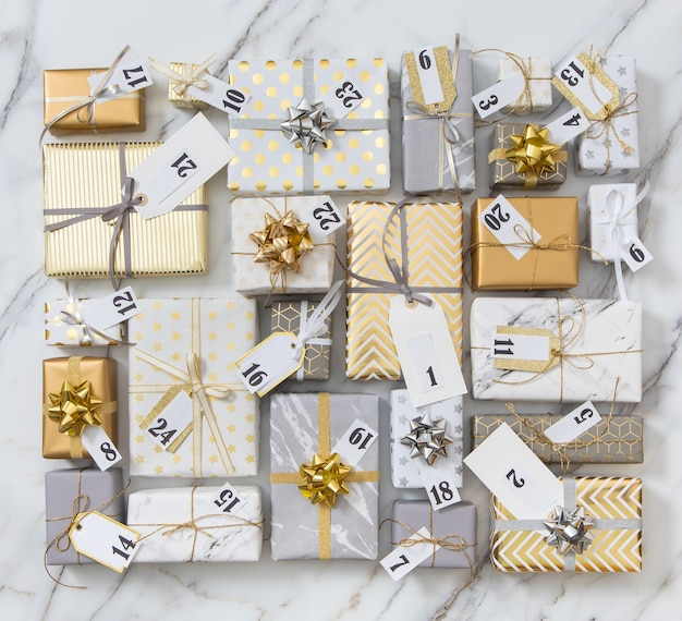 Many gift boxes with labels numbers for advent calendar wrapped in glossy classical pack ready for celebrating holiday