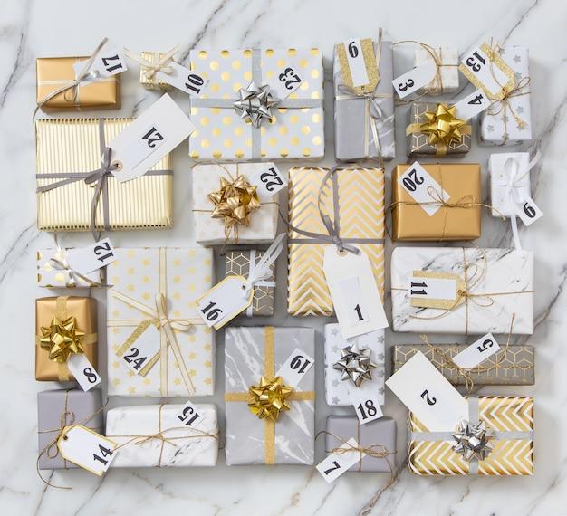 休日を祝う準備ができている光沢のある古典的なパックに包まれたアドベントカレンダーのラベル番号が付いた多くのギフトボックス
