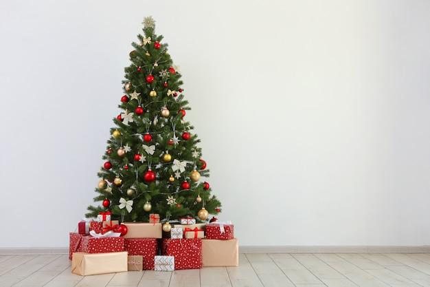 밝은 실내에서 축제로 장식된 크리스마스 트리 아래 많은 선물