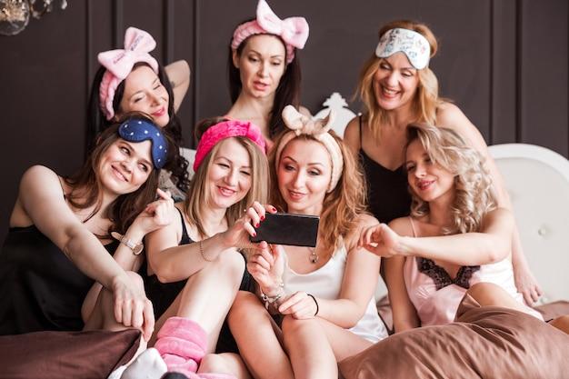 Многие подруги девушек устроили пижамную вечеринку на шикарной кровати. девушки улыбаются, смотрят в камеру и делают селфи.