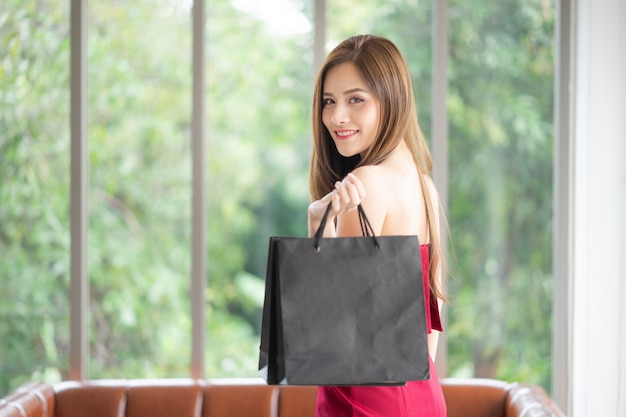 Many girls are shopaholics like her. she is beautiful in red dress, and holding shopping b