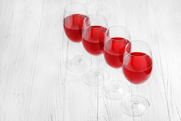 Many glasses of burgundy french wine on a wooden table