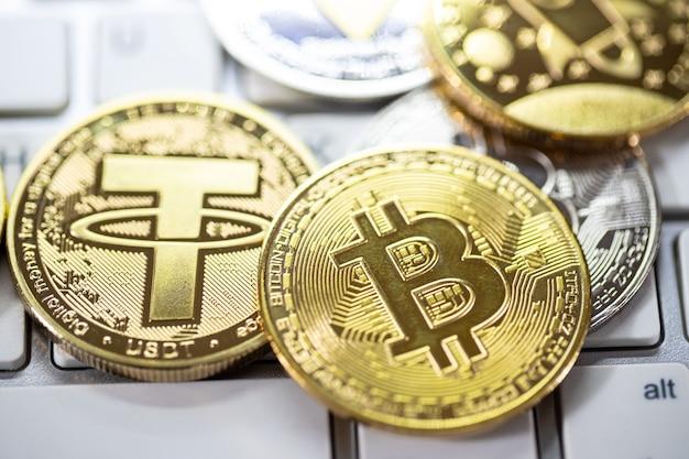 많은 금색 암호화폐 비트코인이 흰색 키보드에 놓여 있습니다., 새로운 가상 화폐. 금화의 성장률은 세계의 미래에 모든 것을 지불하는 중요한 통화입니다.