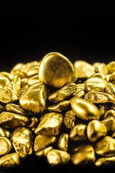 고립된 검은 배경에 많은 금 덩어리, 부와 희귀 광석의 개념