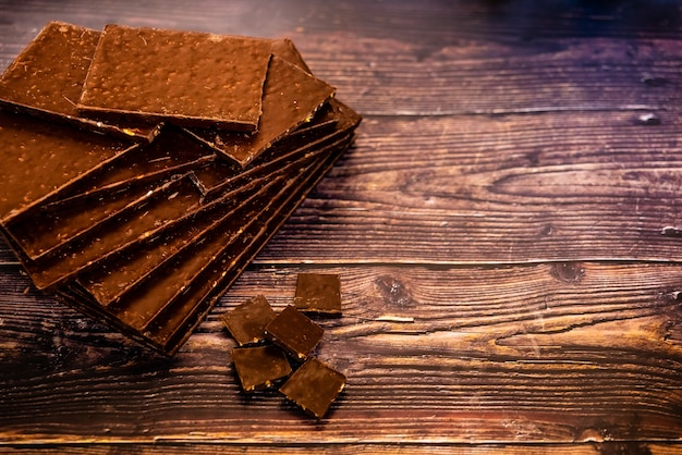 Many gourmet dark chocolate tablets isolated on wooden background.