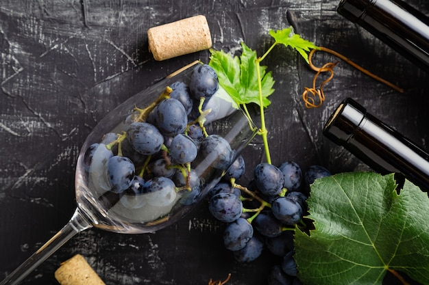 Many grapes in wine glass. wine bottles, grape bunches with leaves and vines wine corks on dark