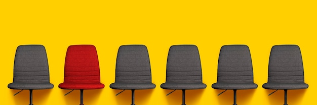 Many gray office chairs and one red chair on a yellow