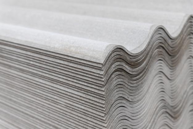 多くの灰色のスレートシートが互いの上に積み重ねられています。波状の縞模様
