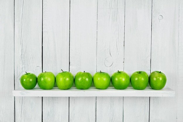 棚にたくさんの青リンゴ。白、木製の背景。