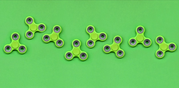 Many green fidget spinners lies on texture background
