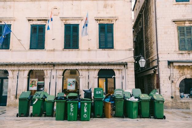 아침 일찍 쓰레기를 제거하는 많은 녹색 쓰레기통
