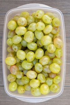 Many green grapes in a plastic box
