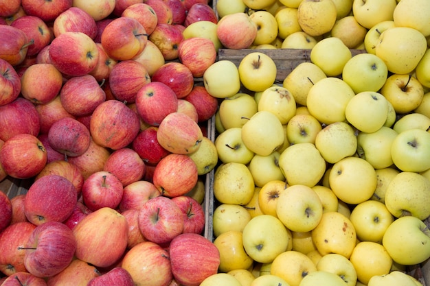 Many green and red apples on shelf as texture background