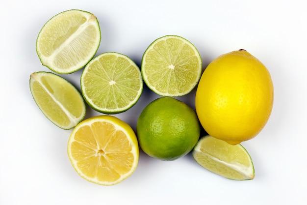 밝은 흰색 테이블에 많은 반쪽과 노란색 레몬과 녹색 라임 조각. 부엌 나무 위에 신선한 과일