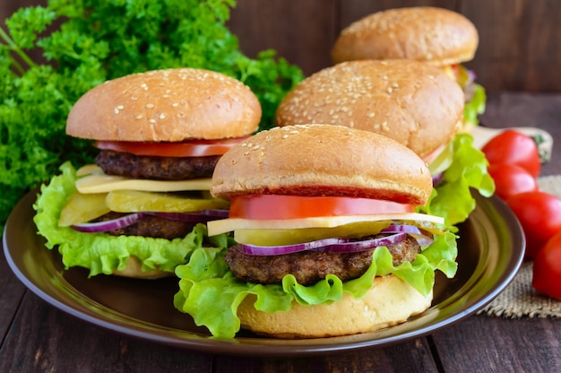 Many hamburgers at home (bun, tomato, cucumber, onion rings, lettuce, pork chops, cheese) in a clay bowl on a wooden background. close-up