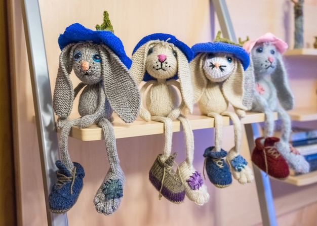 Many hand made knitted sad hares, knitted baby toys