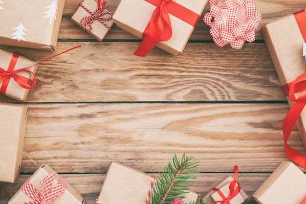 Many handmade christmas gift boxes on wooden background.