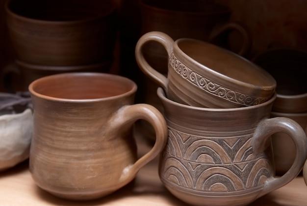 На полке много старых глиняных горшков ручной работы.
