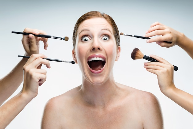 Many hands applying make-up to glamour woman over white background.