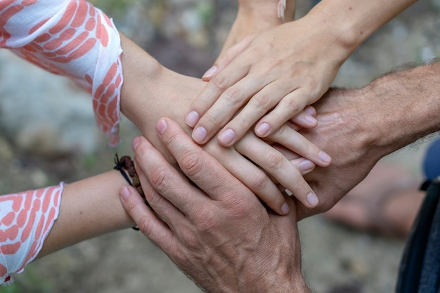 Many hands getting together in the center of a circle