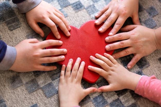 大きな心の上にさまざまな年齢の人々の多くの手